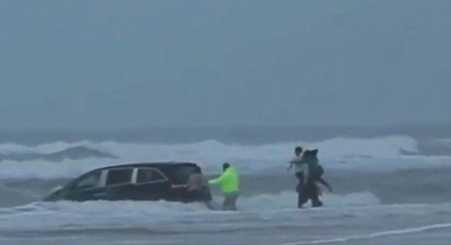 Race against time: The rescuers managed to grab all the children from the car as it was submerged in the surf