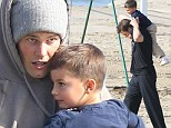 Doting dad Tom Brady gives four-year-old son Benjamin a piggyback ride on the beach in Santa Monica