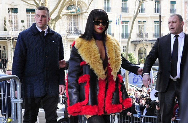 Seeing red: There was no mistaking the pop superstar in her distinctive jacket as she strode part waiting fans to enter the show