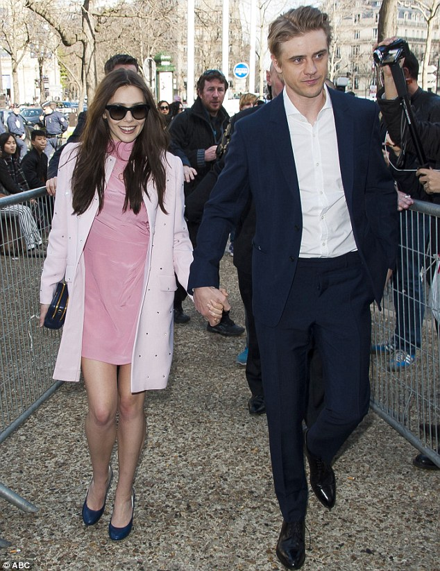 Thinking pink: Elizabeth wore a pale pink coat over her dress a she arrived at the show with boyfriend Boyd Holbrook