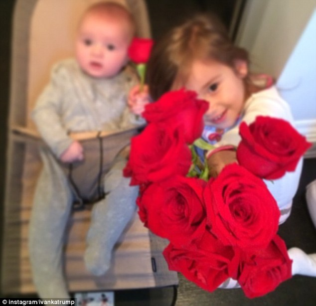 Sibling love: And in a photo shared on Valentine's Day, Joseph sits in his baby chair while his older sister Arabella hold a bouquet of roses up for their mother.