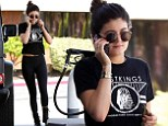 Chatting at the pump! Multitasking Kylie Jenner remains on her cell as she makes gas station visit in black T-Shirt and leggings