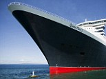 Captain Kevin Oprey stands beneath the soaring hull of Cunard's flagship Queen Mary 2