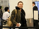 Actor Christian Slater making his way through Miami International Airport with a therapy dog