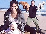 Upward dog: Hilaria Baldwin shared her daily yoga pose picture on Saturday and if featured baby Carmen and husband Alec Baldwin holding up their dogs on a beach