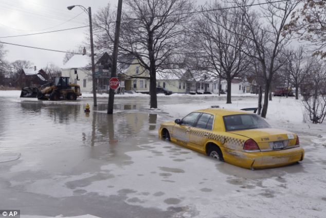 Abandoned: A taxi is submerged on a flooded street after a water main break in Detroit on Tuesday