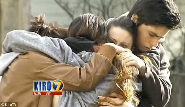 Family: Brad George is pictured here holding his two sisters and a friend the day of his mother's death. He has been arrested and charged by police in Everett for brutally battering Georgina Latshaw to death with a dumbbell on Thursday night/Friday morning