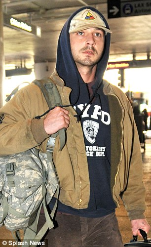 No smiles: The 27-year-old Transformers actor, who is said to be missing a tooth, walked through the airport lobby with clear stains on his beige cap