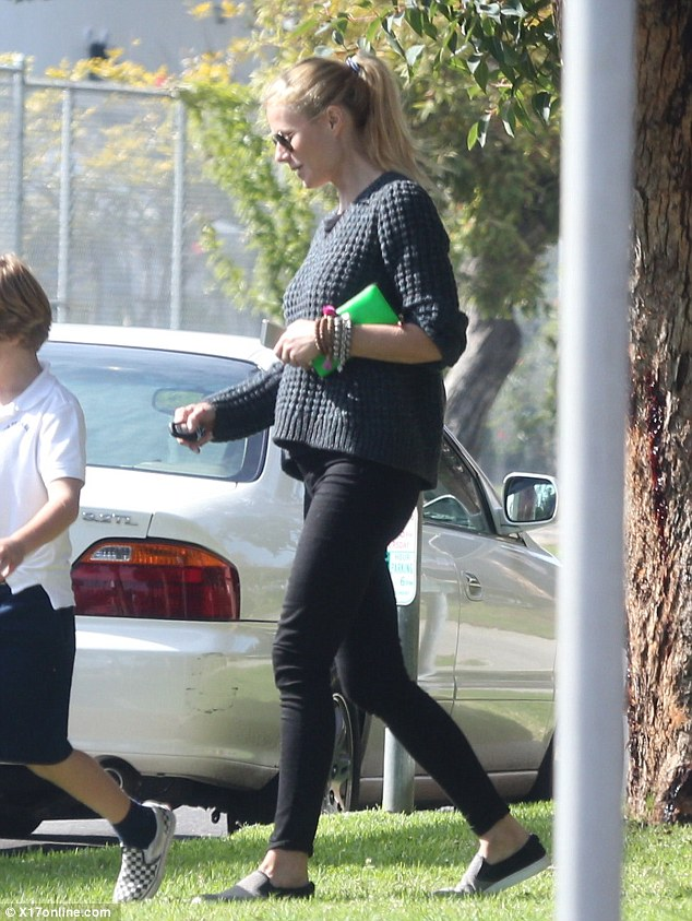 Comfy: A make-up free Gwen wore a homely navy blue knit sweater over black jeans that highlighted her long slim legs and a pair of black and grey slide on shoes