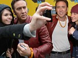A love-bead wearing Nicholas Cage poses with fans and co-stars at the 2014 SXSW Music, Film + Interactive Festival Sunday in Austin, Texas