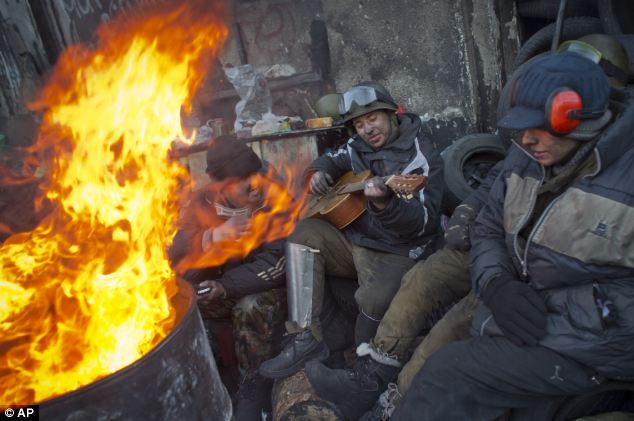 Anti-government activists entertain themselves next to a fire at a barricade in central Kiev