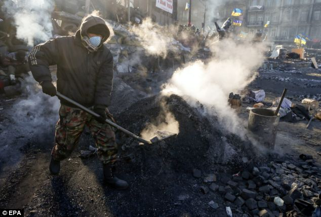 Protesters clean the area near a barricade during the continuing protests