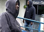 He's slumming it! Normally done up Kanye West goes casual as he tours through a favela in Brazil wearing a black hoody