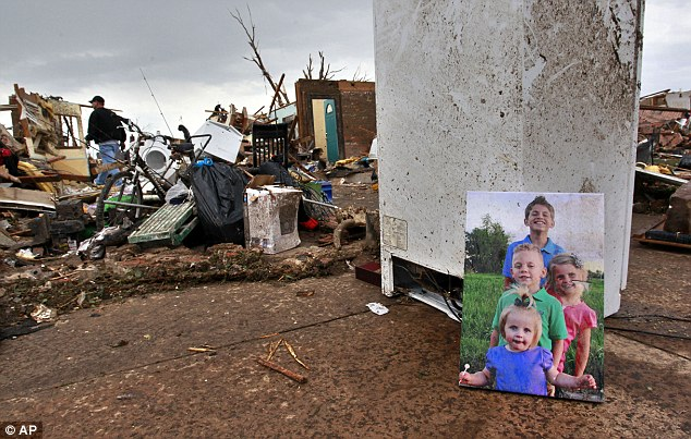 Destroyed: Piles of precious belongings could be seen on streets destroyed by Monday's tornado