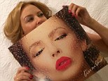 Album covered: Diminutive Kylie Minogue lies on a bed, almost completely obscurred by the LP version of the cover art to her new album Kiss Me Once - out on March 18