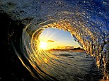 Early morning shot: Sun rays burst through the arc of a wave on the North Shore in Oahu, Hawaii in this photo snapped by travel photographer Clark Little