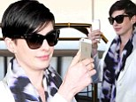 Cinematographer in the making? Anne Hathaway whips out her cell phone and shoots a video as she lands in LAX with her husband