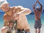 Who's monkeying around now! Shirtless Kellan Lutz flexes his muscly body on 'The Beach' in Thailand