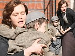 Protective: Carey Mulligan was seen cradling her young co-star as she filmed Suffragette in London on FRiday