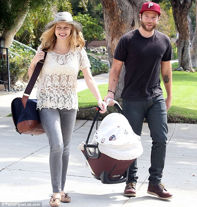 Happy family: The new mother looked utterly delighted as she went for a stroll in Los Angeles with her husband Mark Webber and new bundle of joy on Tuesday