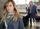 Where's Bradley when you need him? Suki Waterhouse steps out spotty neck scarf and skinnies as she wheels cases into Heathrow