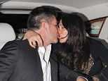 Back-seat smooch! Simon Cowell shares a tender kiss with Lauren Silverman in his car during night out... after buying mag from homeless man