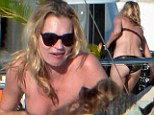 Fun in the sun: Kate Moss relaxes alongside Sir Philip Green after helping him celebrate his 62nd birthday