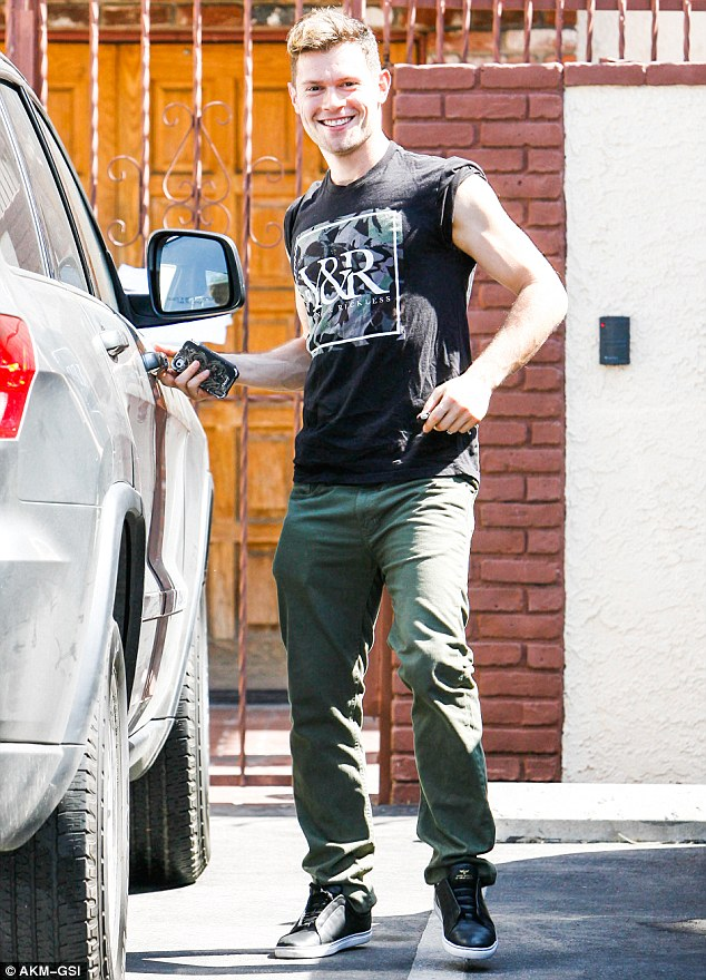 All smiles: Professional dancer Henry Byalikov wore a casual black shirt over olive green pants, with black sneakers