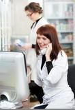 Pharmacy chemist women in drugstore with phone