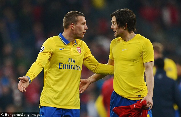 Frustrated figures: Lukas Podolski (left) and Tomas Rosicky (right) argue after Arsenal's Champions League exit to Bayern Munich