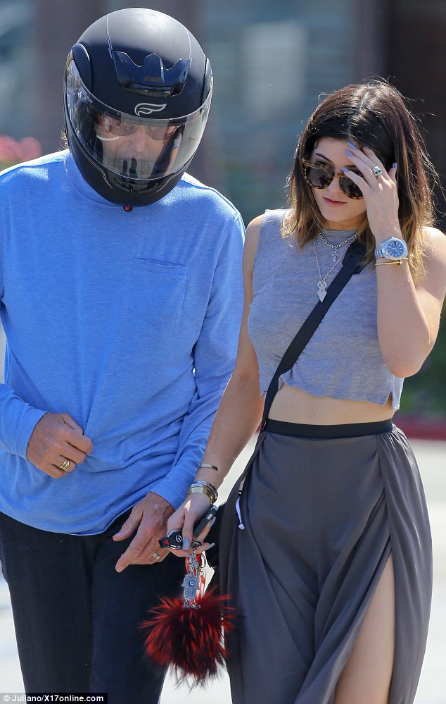 Heavily accessorised: Kylie wore a selection of jewellery including rings, chains, bracelets and a watch as she hung out with her dad