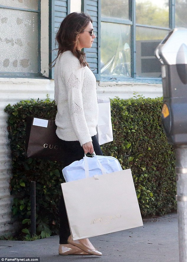Hiding something? Mila looked cool and cosy in a baggy white sweater, black skinny jeans and nude ballet flats