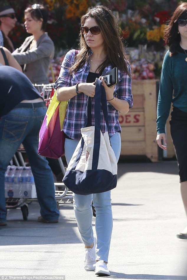 Clever cover up: The beauty shields her tummy with a tote bag while leaving Trader Joe's on Thursday