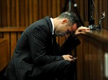 On trial: Oscar Pistorius checks his mobile phone as he sits in the dock waiting for the proceedings of his murder trial to begin at the High Court in Pretoria, South Africa, on Tuesday