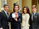 Recognition: Karren Brady holding her CBE outside Buckingham Palace with her husband - former footballer Paul Peschisolido - and children Sophia and Paolo