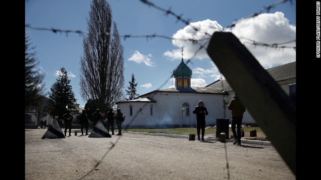 Armed soldiers stand guard outside a Ukrainian military base in Perevalne, a village in Crimea, on March 17.