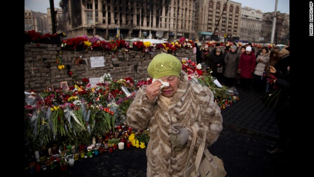 A woman cries February 24 near a memorial for the people killed in Kiev.