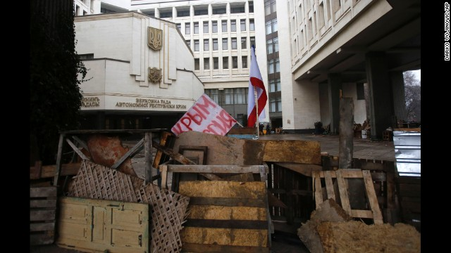 """Barricades in front of a government building in Simferopol on February 27 hold a banner that reads: """"Crimea Russia."""" There's a broad divide between those who support the pro-Western developments in Kiev and those who back Russia's continued influence in Crimea and across Ukraine."""