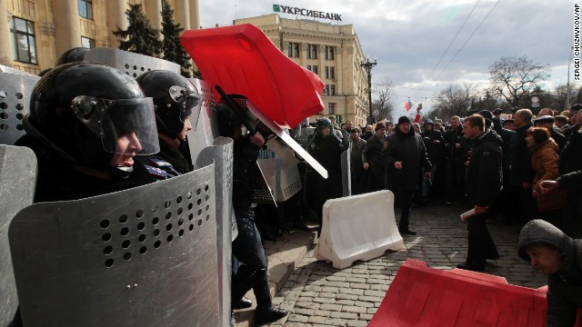 A Ukrainian police officer tries to shield himself from a road block thrown by pro-Russia supporters in Kharkiv, Ukraine, on March 16.