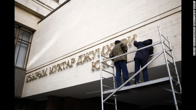 Letters on the front of the Crimean Parliament building are removed Tuesday, March 18, in Simferopol after voters in the territory voted to join Russia and break away from Ukraine. Russia's military activities in Crimea and its backing for the region's secession bid have been condemned by Ukraine's interim government in Kiev, the European Union and the United States. The standoff has sparked an international crisis, reviving concerns of a return to Cold War relations.