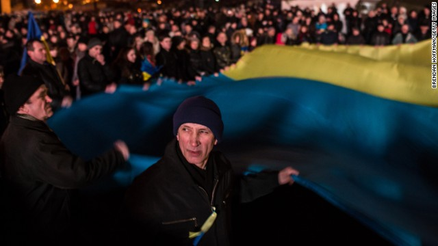 People wave a large Ukrainian flag in Independence Square on Sunday, February 23.