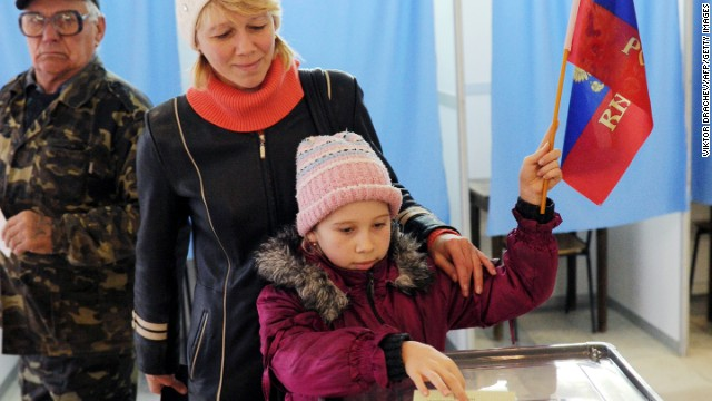 A child casts her mother's ballot March 16 while holding a Russian flag at a polling station in Simferopol.