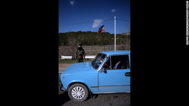An armed Cossack stands guard at a checkpoint on the road from Simferopol to Sevastopol on March 13.