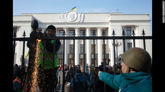 Protesters remove a fence that surrounds Ukraine's parliament in Kiev on February 26.