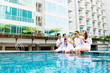 Asian Friends sitting by hotel swimming pool