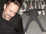 David Arquette looks to be in high spirits as he lays in the middle of the road in front of a stop sign after leaving his Bootsy Bellows Nightclub