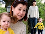 Smile! Alyson Hannigan followed as her 22-month-old daughter Keeva toddled along in a bright yellow smiley face sweater in Los Angeles on Thursday