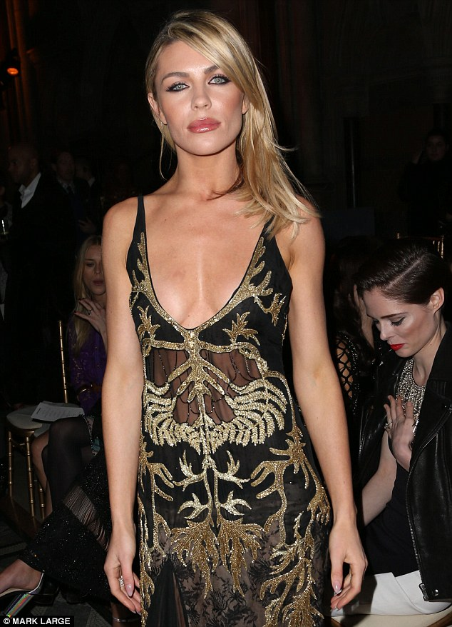 Dare to bare: Abbey, 28, a close friend of the Welsh fashion designer, opted for a rather revealing ensemble as she took her place at the show, showing off plenty of skin in a plunging black and gold semi-sheer gown