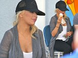 Christina Aguilera reveals hint of baby bump for first time in a tank top and tights after 'pregnancy news'