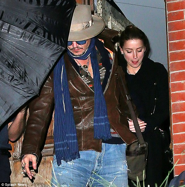 In case of rain: The pair walked beneath an umbrella as they exited the New York home